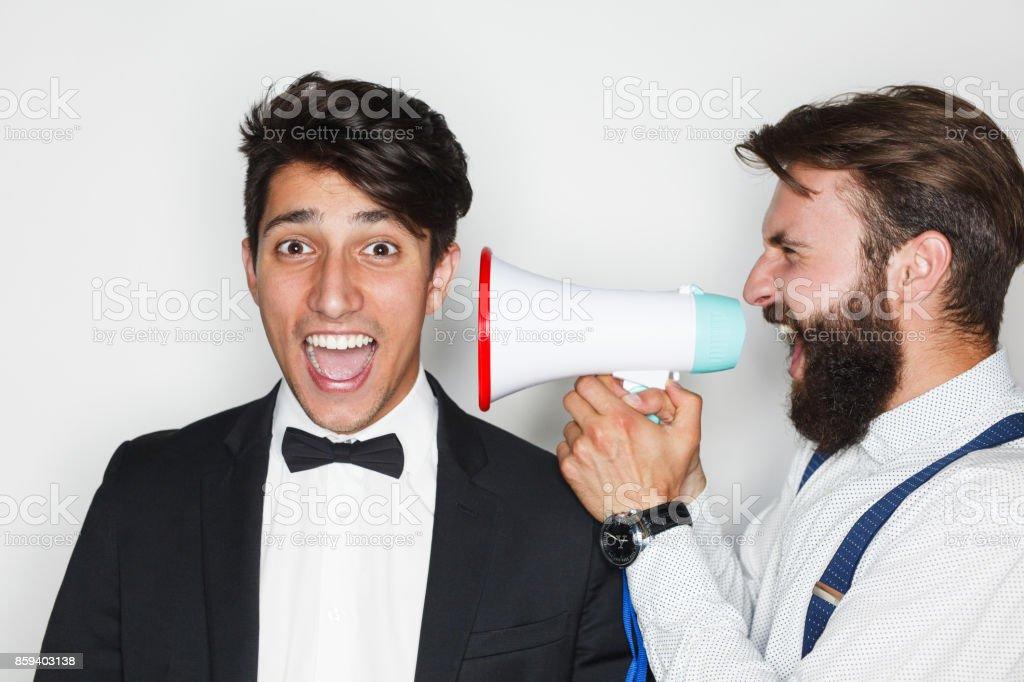 Two men having fun with loudspeaker stock photo