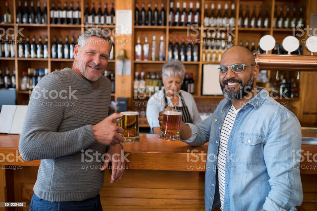Two men having glass of bear at counter in restaurant stock photo