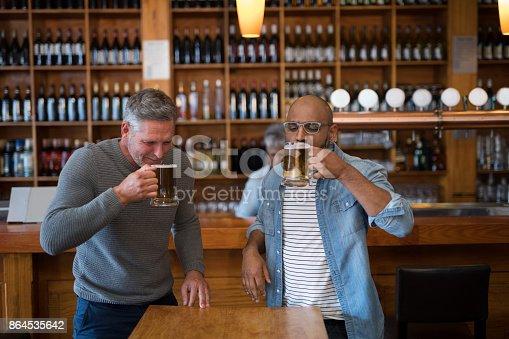 istock Two men having glass of bear at in restaurant 864535642