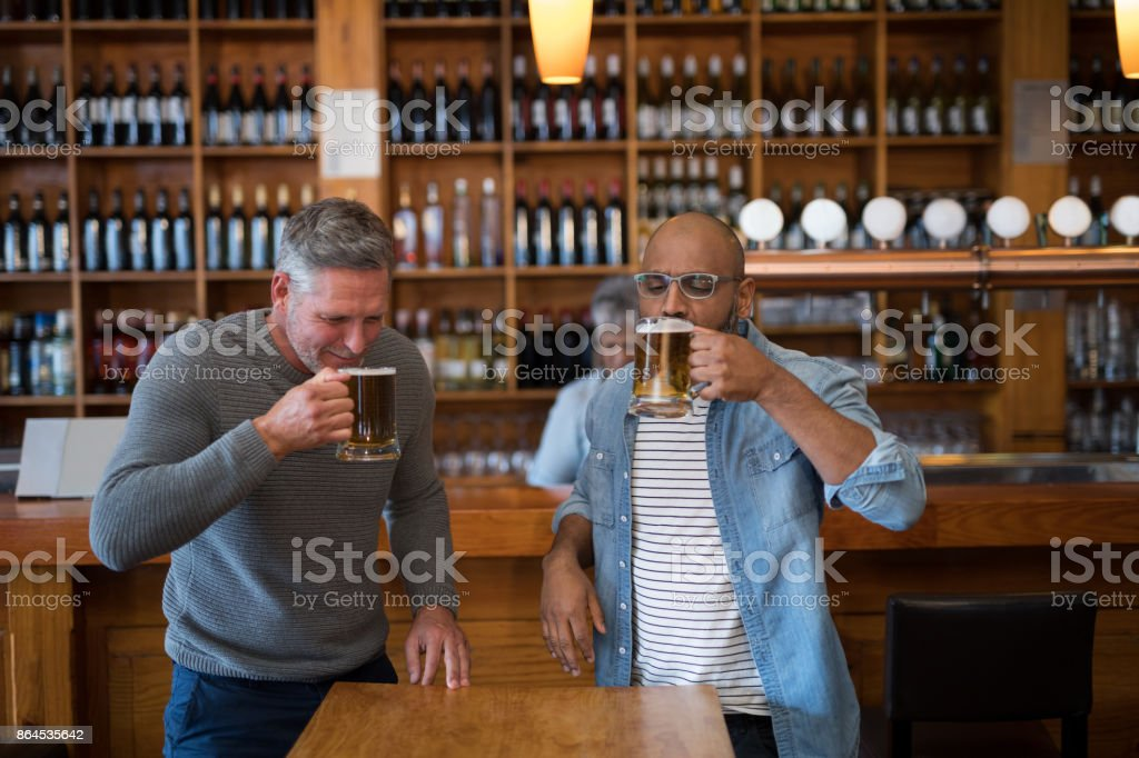 Two men having glass of bear at in restaurant stock photo