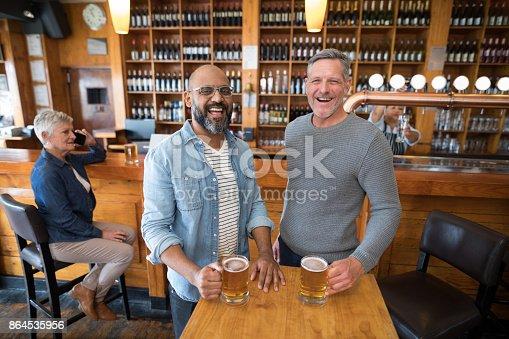 istock Two men having glass of bear at in restaurant 864535956