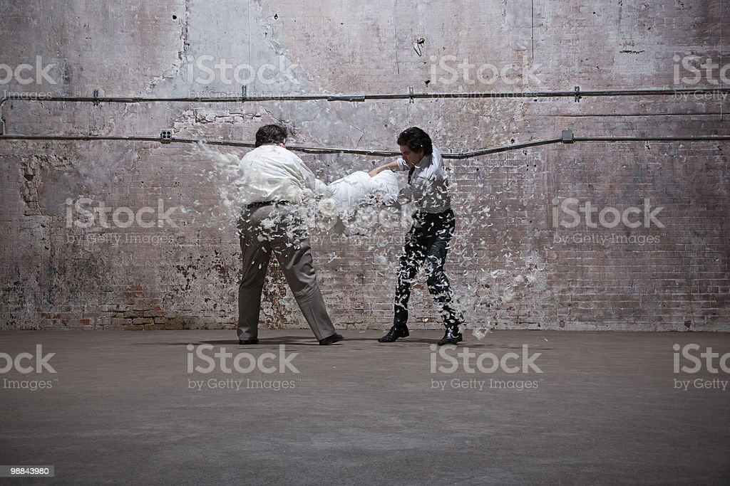 Two men having pillow fight in warehouse royalty-free stock photo