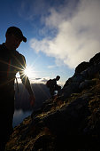 Two men in silhouette climbing a steep mountain side on Senja island in Northern Norway.