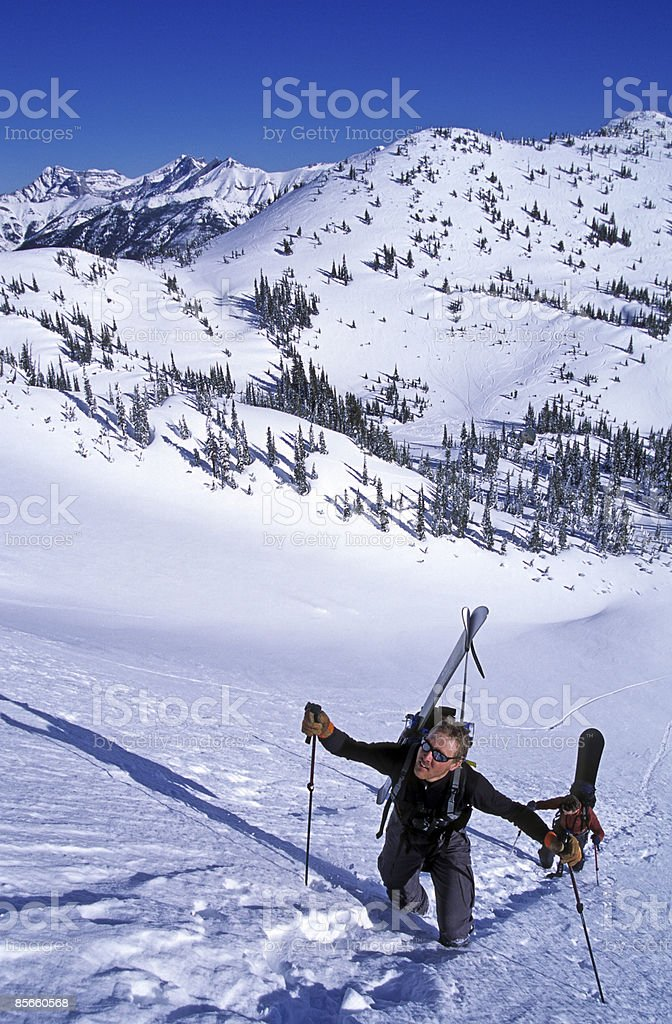 Two men hiking steep slope to ski. royalty-free stock photo