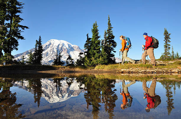 Two men hiking with Mt. Rainier in the background stock photo