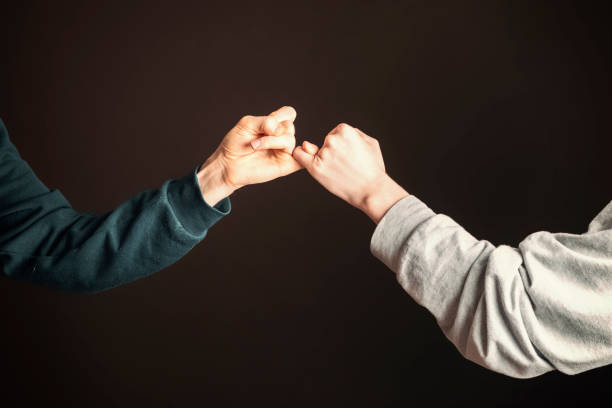 two men hold their little fingers and make peace d s - pinky promise stock photos and pictures