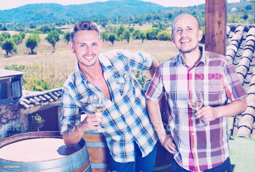 Two positive smiling men holding glass with sparkling wine outdoors...