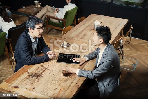 istock Two men in a casual meeting in a Cafe 584892002