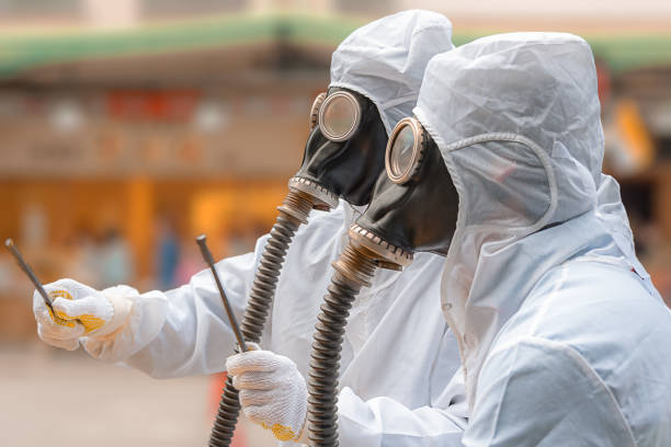 two men in bio-hazard suits and gas masks. - white suit stock photos and pictures