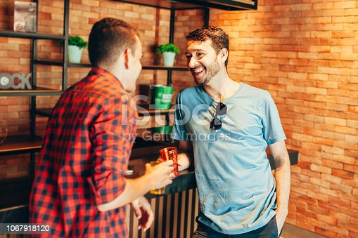 Two men in casual clothes having a conversation at bar counter in pub