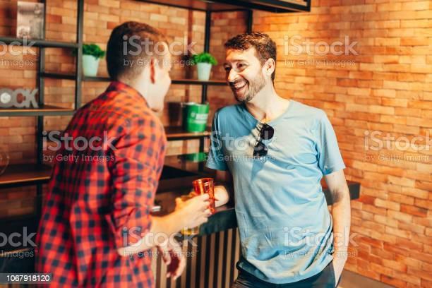 Two men in casual clothes having a conversation at bar counter in pub picture id1067918120?b=1&k=6&m=1067918120&s=612x612&h=9mgdv8ocvvqg9zv9qxh  kseakcxb s n s6dueygs0=