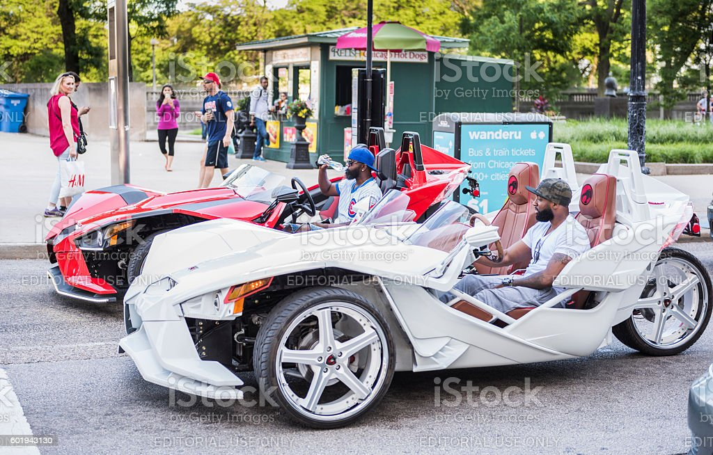 Two men in flashy red and white Polaris Slingshot stock photo