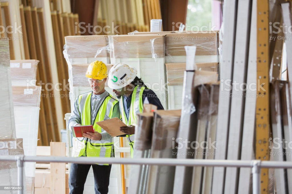 Two men in hardhats looking at warehouse inventory list stock photo