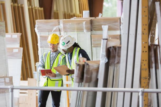 deux hommes en casques en regardant la liste de l'inventaire d'entrepôt - matériau de construction photos et images de collection