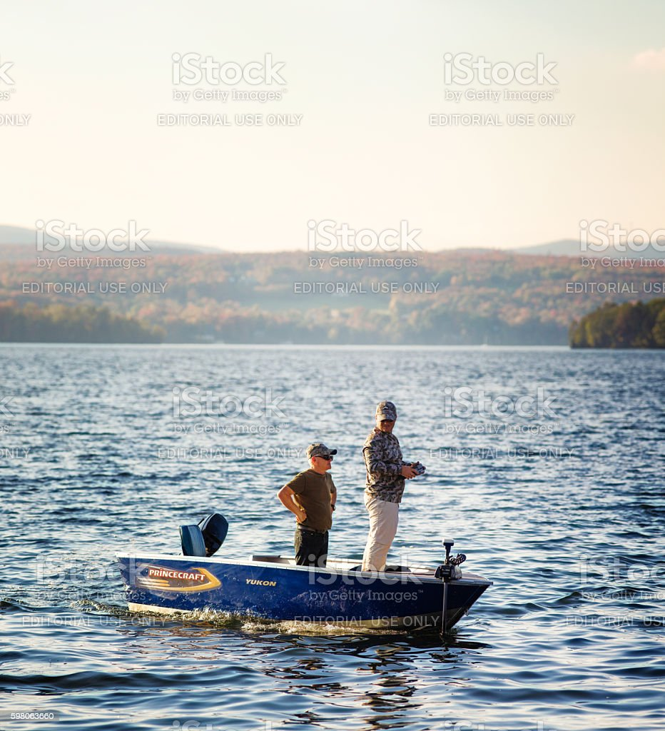 Two men in small boat using remote sensor at sunset stock photo