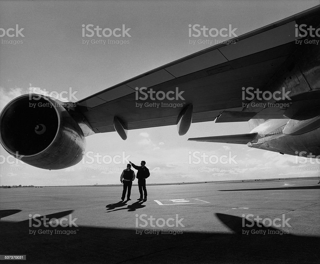 two men inspecting a jet wing and engine. stock photo