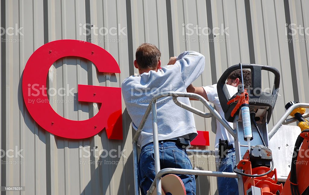 Two men installing a red sign on a building stock photo