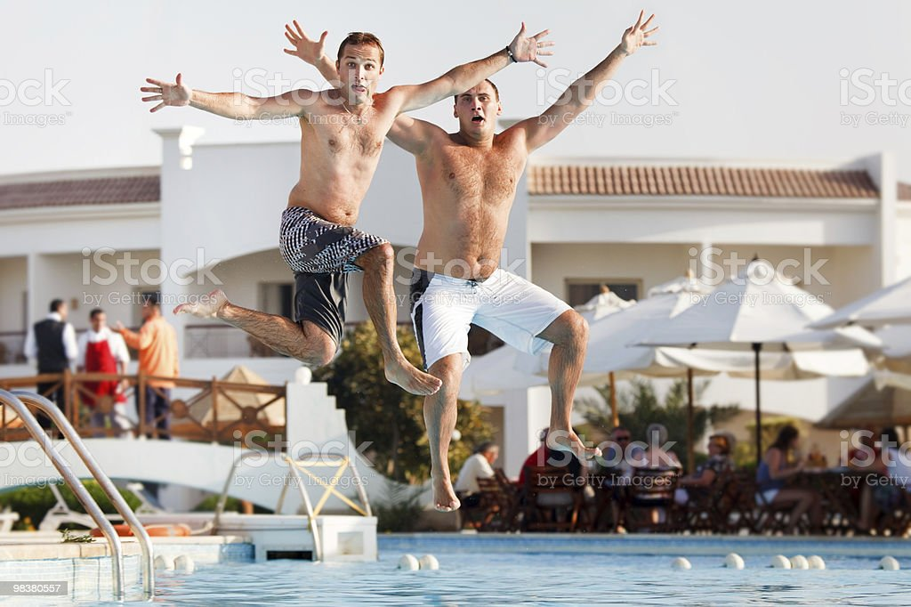 Two men jumping in swimming pool royalty-free stock photo