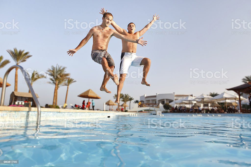 Two men jumping in swimming pool together royalty-free stock photo