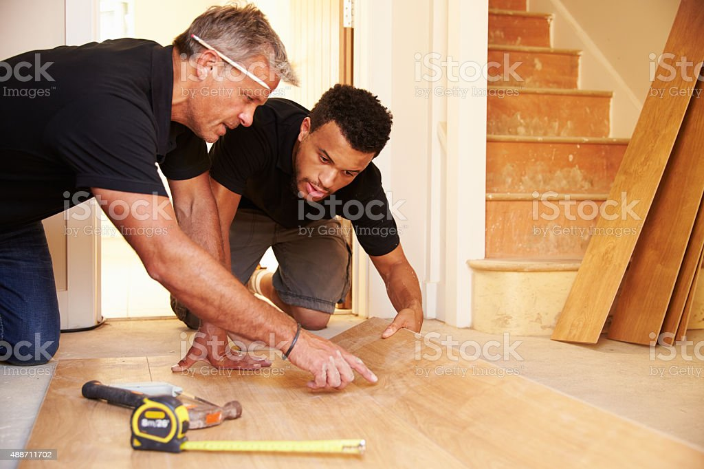 Two men laying wood panel flooring in a house stock photo