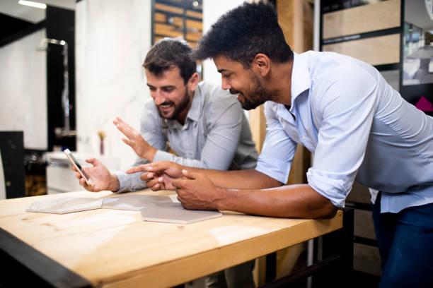 Zwei Männer, die sich mit sechseckigen Holzfliesen bedeckt über den Schreibtisch lehnen und in einem Geschäft gemeinsam auf ein Mobiltelefon schauen – Foto