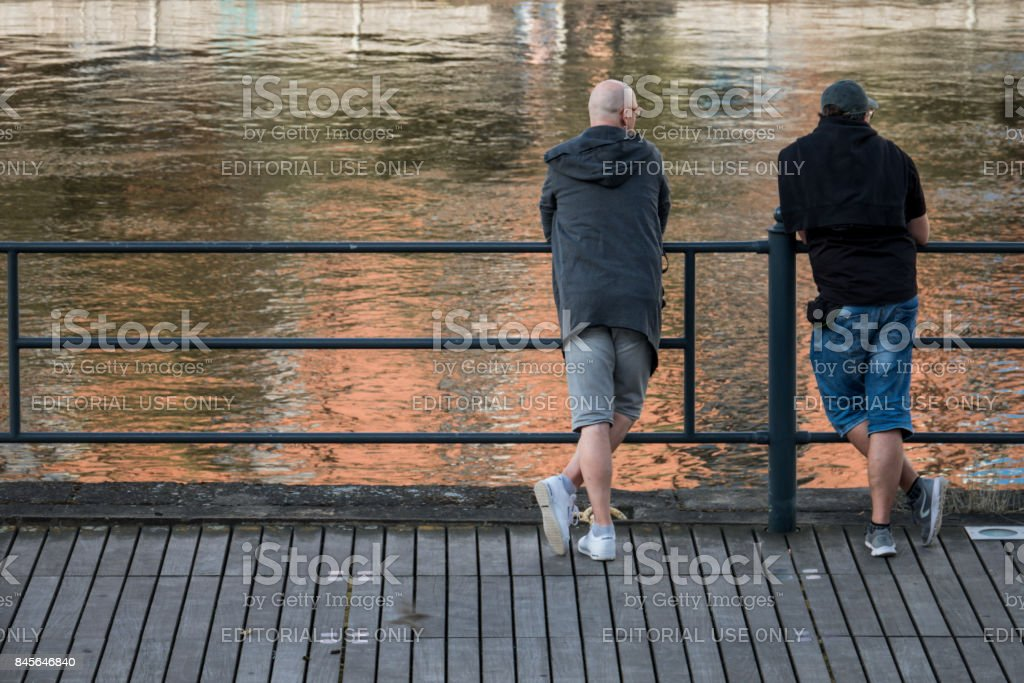 Two men looking at a flowing river stock photo