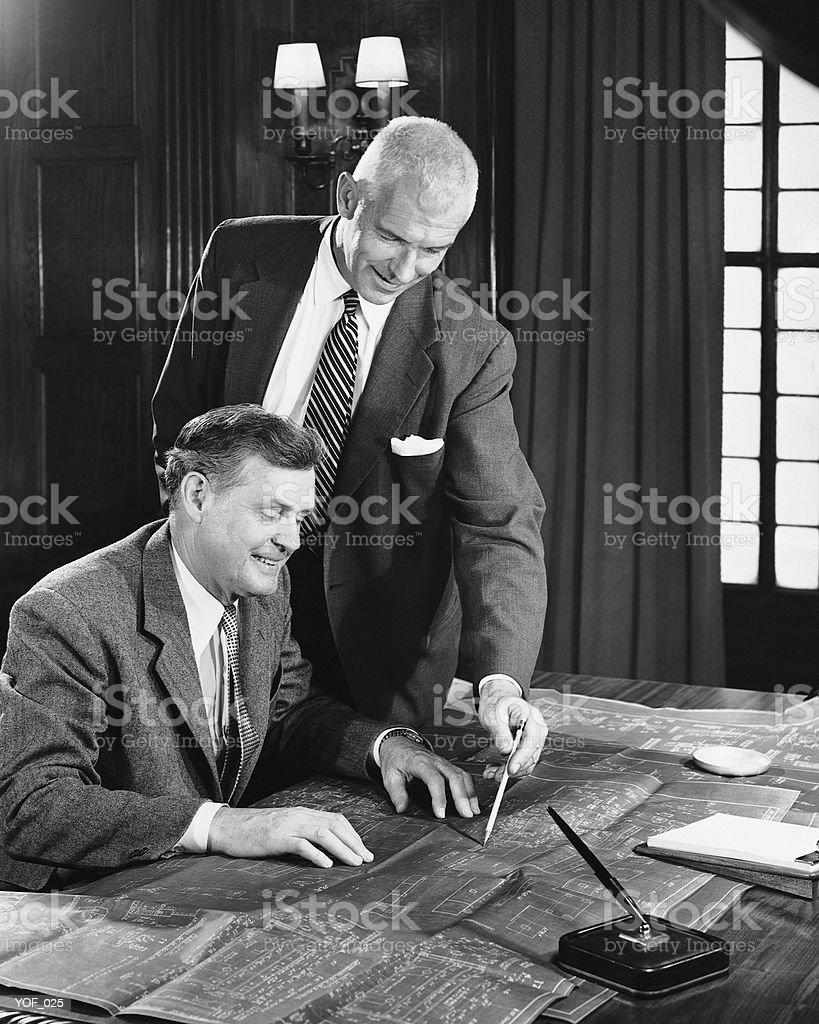 Two men looking at blueprints royalty-free stock photo