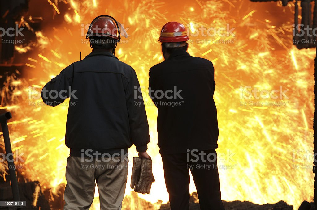 Two men looking at the molten iron splashing royalty-free stock photo