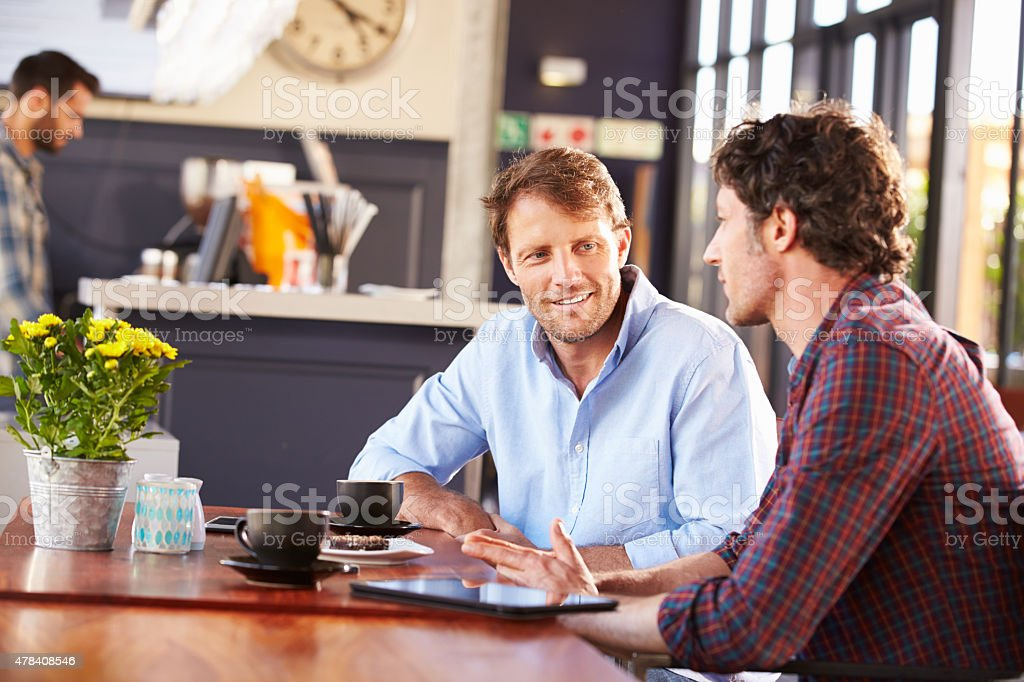 Two men meeting at a coffee shop stock photo