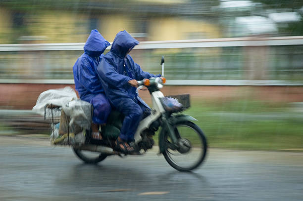 two men motorcycling through the rain in hoi an, vietnam - motorbike, umbrella stock pictures, royalty-free photos & images