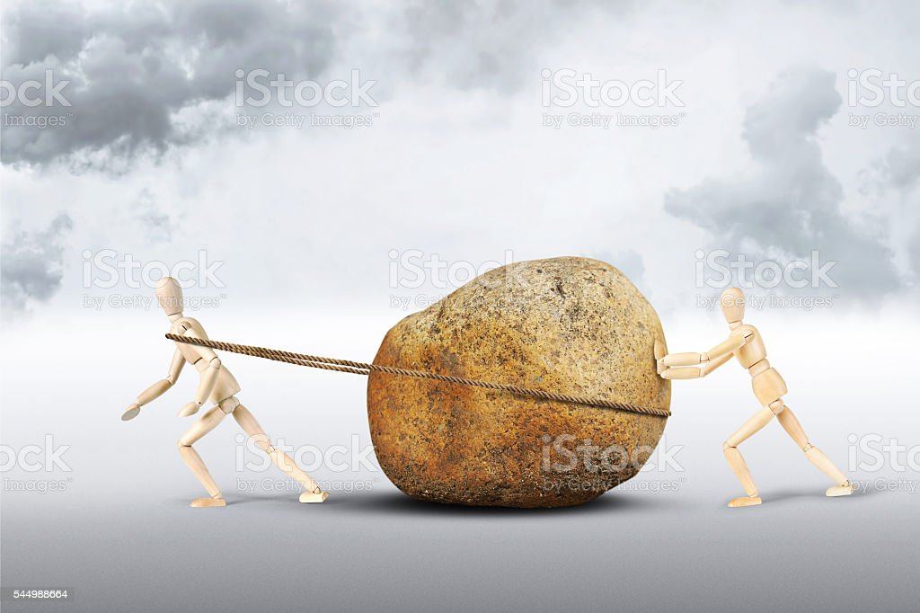 Two men move a huge stone stock photo