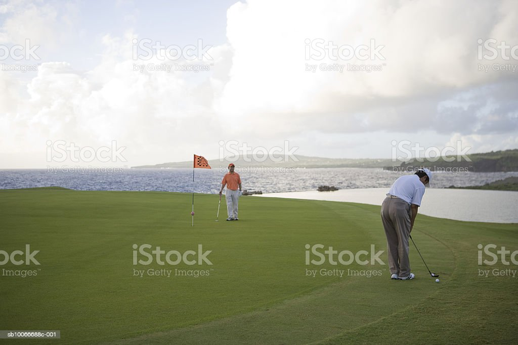 Two men on golf course, one watching and another putting golf ball 免版稅 stock photo