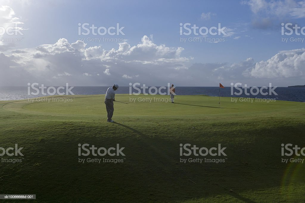Two men on golf course, one watching and another putting golf ball royalty-free stock photo