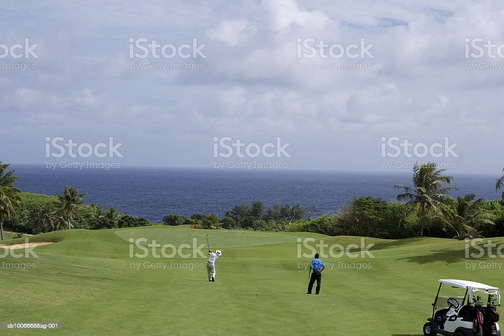 Two men on golf course, one watching and another putting, rear view royalty-free stock photo