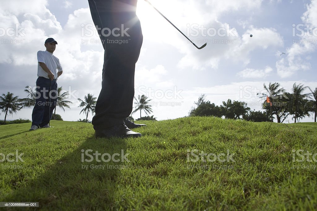 Two men on golf course playing golf, low angle view royalty-free stock photo