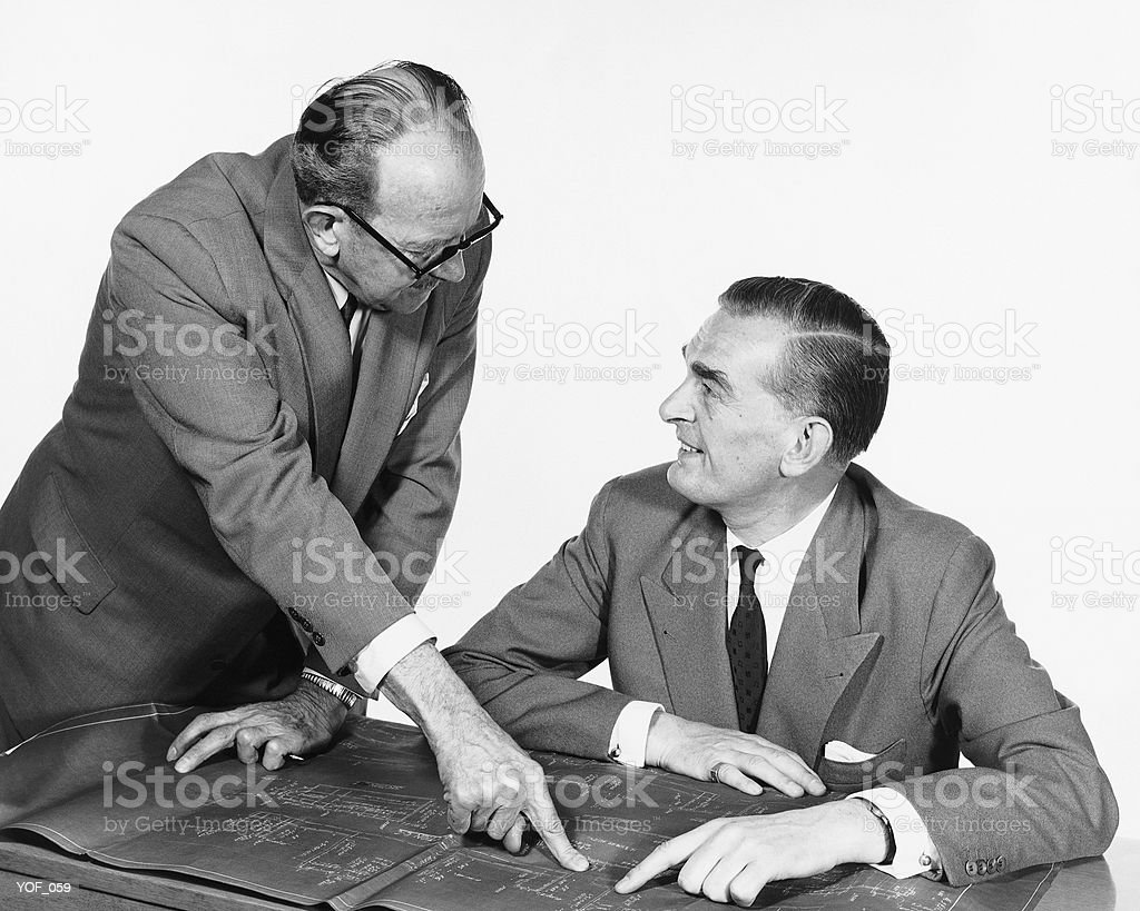 Two men, one pointing to blueprint royalty-free stock photo
