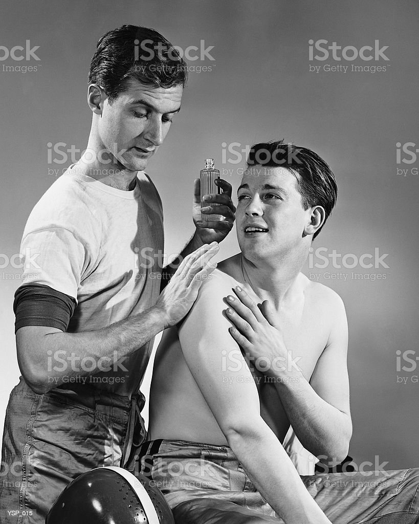 Two men, one rubbing liniment on other's shoulders royalty-free stock photo