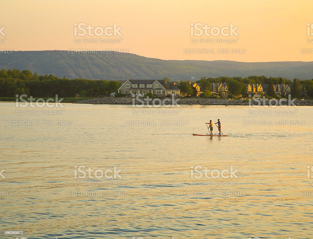 Two Men Paddleboarding at Dusk Collingwood stock photo