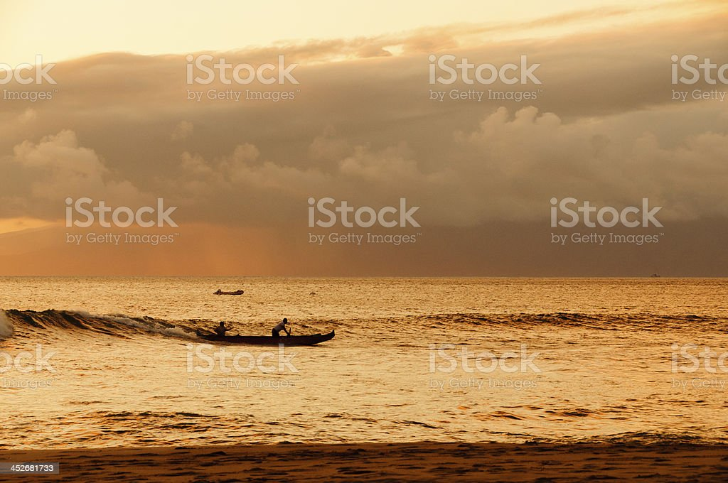 Two men paddling a Hawaiian outrigger canoe at sunset. stock photo