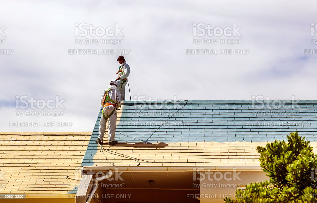 Two men painting a roof of a house stock photo
