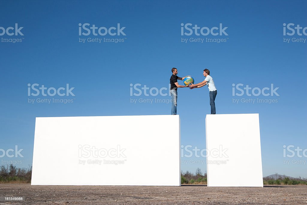 Two men passing globe outdoors royalty-free stock photo
