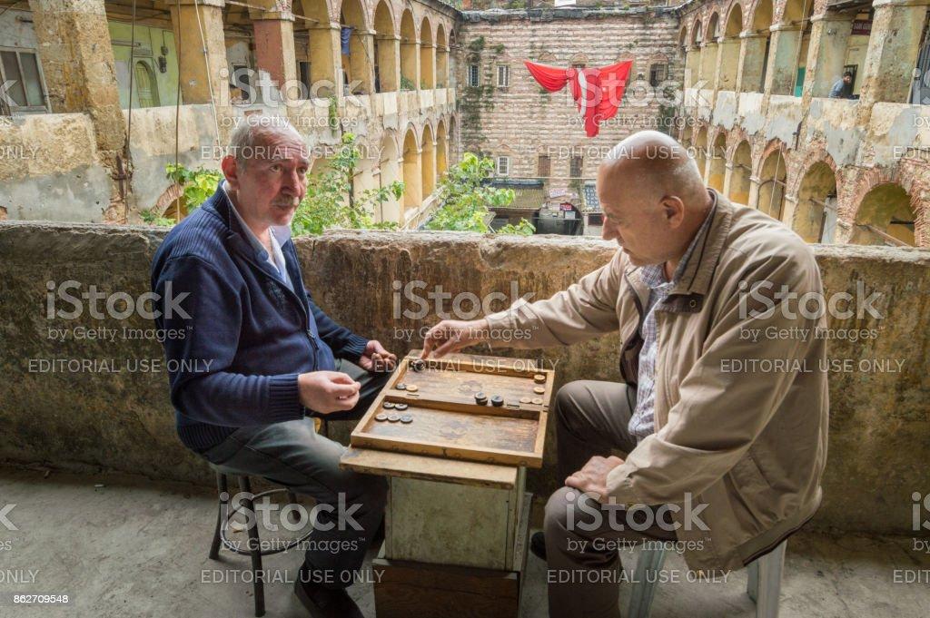 Two men playing backgammon in the old caravanserai Büyük Valide Hani in Istanbul, Turkey stock photo