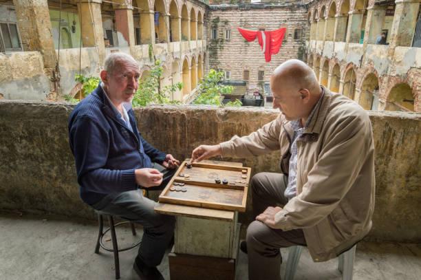 twee mannen backgammon spelen in de oude karavanserai büyük valide hani in istanboel, turkije - karavanserai stockfoto's en -beelden