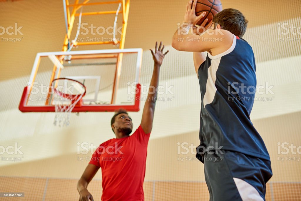 African-American man trying to stop contender from throwing ball into...