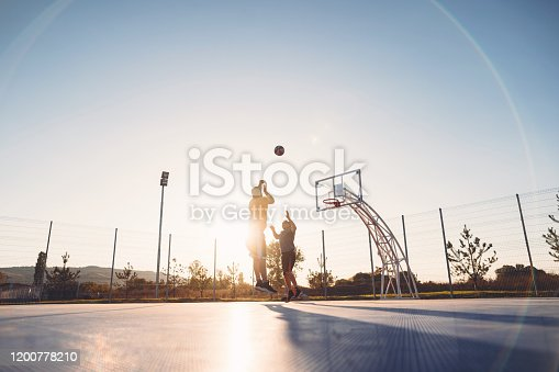 Senior father playing basketball on a outdoor sports court with his son, enjoying the game on a sunny day.