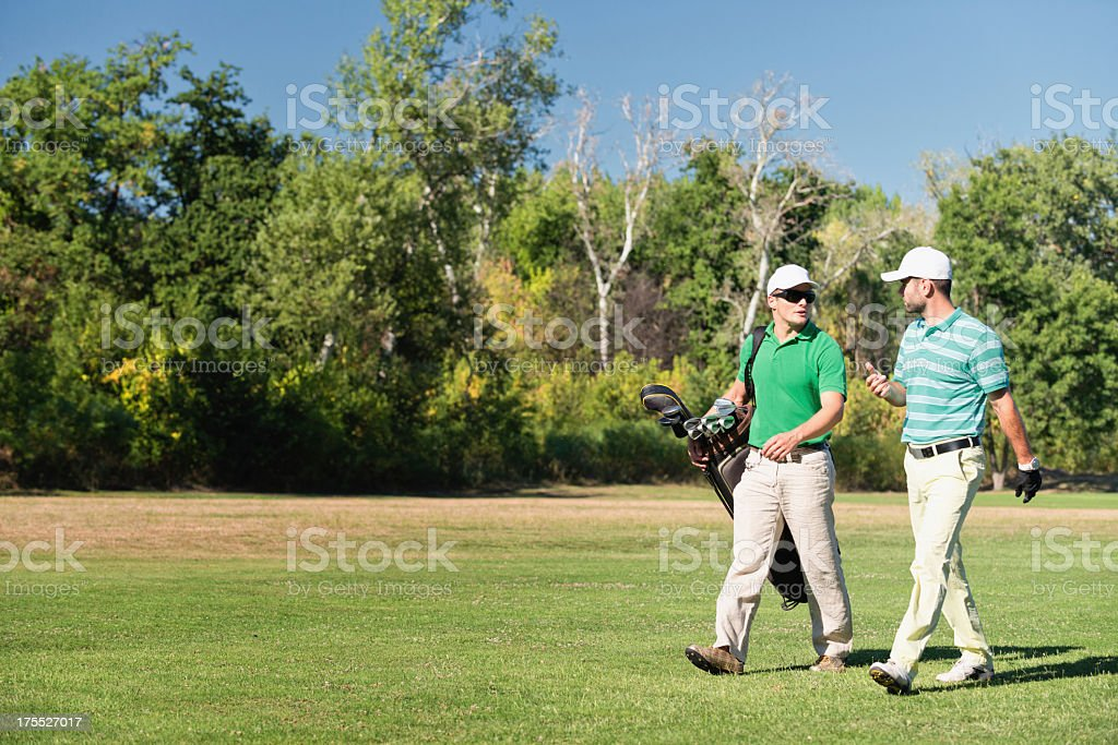 Two men playing golf on a summer day stock photo
