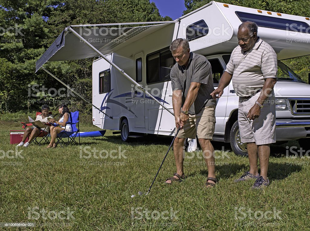 Two men playing golf, women sitting in background foto de stock royalty-free
