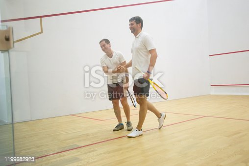Squash players shaking hands after the game on squash court