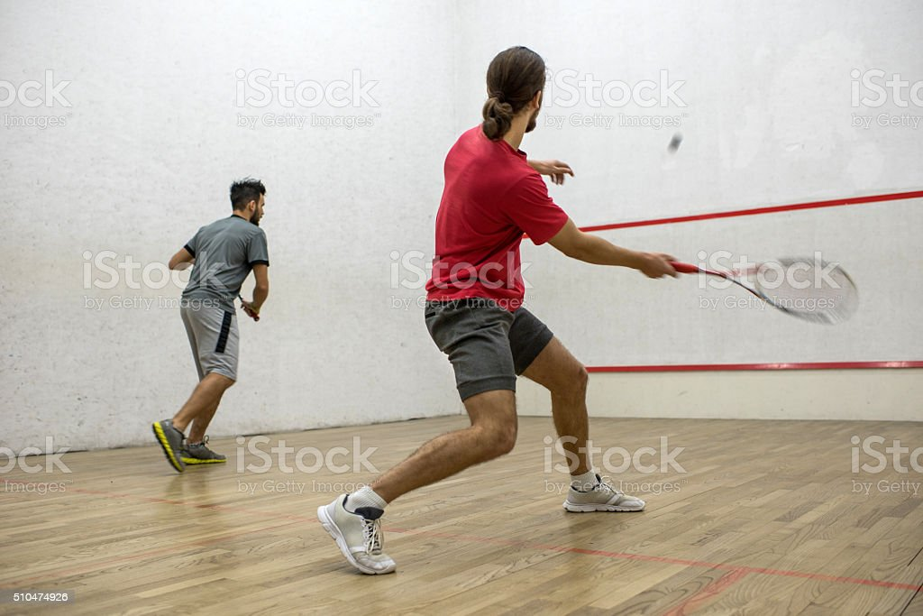 Two men playing racketball on a court. stock photo