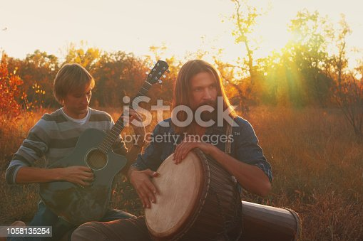 Two men playing the guitar and djembe drum in the autumn in a field.